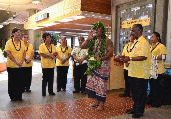 Roberts Hawaiʻi employees gather for the blessing of their new Maui Airport Shuttle service, led by Kahu Kimokeo Kapahulehua at the main lobby of Kahului Airport. Courtesy photo, Lulu Unemori.