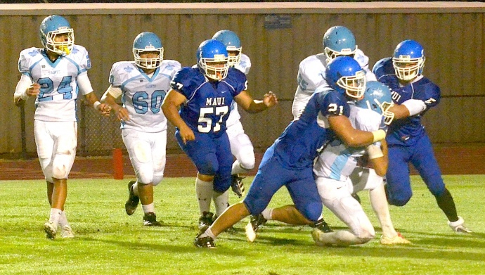 Maui High linebacker Moana Vainikolo (21) sacks Saint Francis' quarterback Blaze Umiamaka before teammates Brysen Kokubun (5) and Kyson Prest (57) can close.  The Sabers beat the Saints 51-0. Photo by Rodney S. Yap.