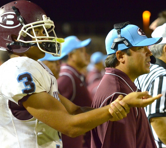 Baldwin offensive coordinator Dave Carino (right) and starting quarterback Jeremiah Badillo (left) signal the play to backup signal-caller Josiah Maglente-Tonu. Photo by Rodney S. Yap.