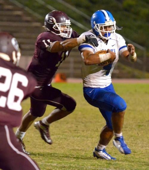 Baldwin linebacker Nohea Keahi (11) wrestles down Maui High running back Onosai Emelio (4). Photo by Rodney S. Yap.