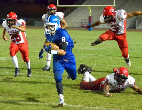 Maui High's Tyson Takabayashi (8) runs away from the Lahainaluna pursuit, including