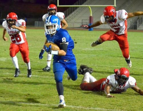 Maui High's Tyson Takabayashi (8) runs away from the Lahainaluna pursuit, including