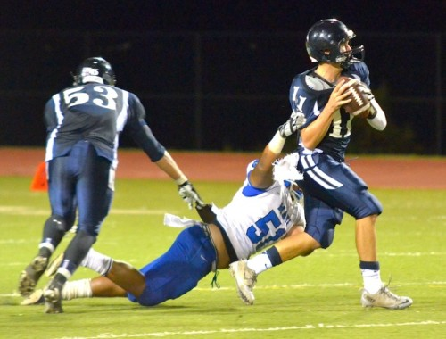 Maui High's Tony Mafileo gets a hand on Kamehameha Maui quarterback Chase Newton (11). Photo by Rodney S. Yap.