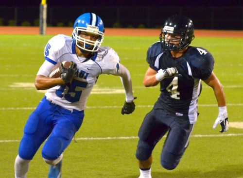 Maui High's Jared Kapisi fakes the punt and runs for a first down as Kamehameha Maui's Rusty Hue Sing gives chase. Photo by Rodney S. Yap.