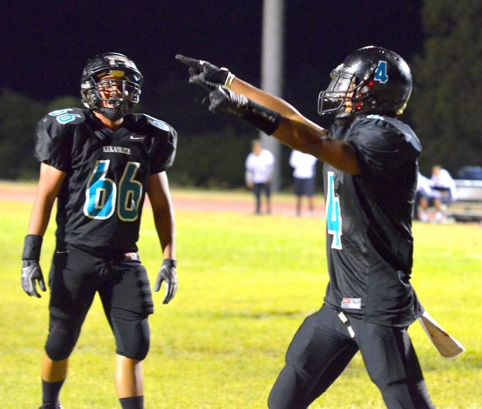King Kekaulike's Kawika Homalon (4) points to the fans following his 1-yard touchdown run in the third quarter. Teammate Izaiah Manrique (66) looks on. Photo by Rodney S. Yap.