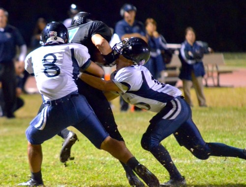 Kamehameha Maui's Austin Kan Hai (5) puts his helmet on King Kekaulike's Charles Apuna after he catches a flat pass from quarterback Ryley Widell. Also helping to bring down Apuna is the Warriors' Michael Kahula. Photo by Rodney S. Yap.