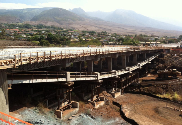 The new bridge, seen above under construction, utilizes an inverted tier arch design, which places arched support beams below the road surface rather than above. This design was selected to minimize obstructions of ocean views for motorists and the Lahaina community. Photo courtesy state Department of Transportation.