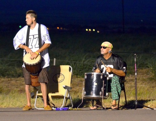 """Maui Lani residents and brothers Dane (left) and Neil Sorensen decided to wake up early Sunday morning to show their support for the Maui Marathon runners. The two set up their drums and amp just the traffic light near Maui Lani golf course headed to West Maui. """"We just felt like showing them some support. We're not runners, but we can appreciate what they are doing,"""" said Neil Sorensen. Photo by Rodney S. Yap."""
