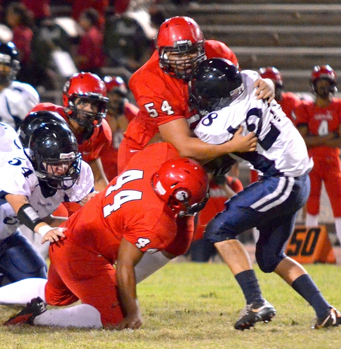 Lahainaluna's Connor Mowat (54) and Bronson Kaina (44) go high and low on Kamehameha Maui running back Ian Armitage (28). Photo by Rodney S. Yap.