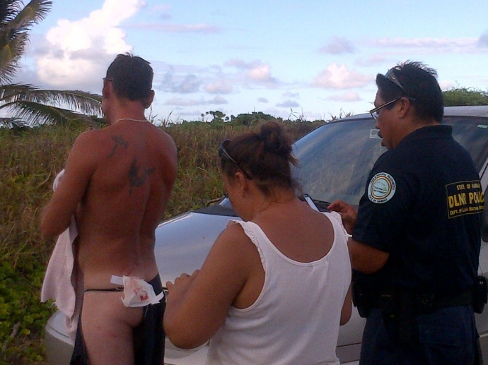 DLNR officers take a look at the apparent shark bite wound. Photo by Wendy Osher.