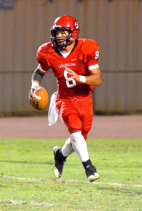 Lahainaluna quarterback Makoa Filikitonga scans the field while rolling to his left. Photo by Rodney S. Yap.