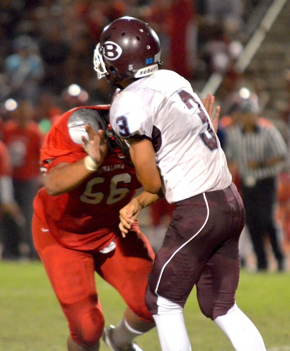 Lahainaluna defensive end Peni Taufa forces Baldwin quarterback Jeremiah Badillo (3) to get rid of the ball early. Photo by Rodney S. Yap.