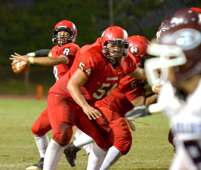 Lahainaluna quarterback Makoa Filikitonga eyes an open receiver from in the pocket behind center Connor Mowat. Photo by Rodney S. Yap.