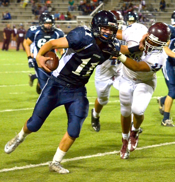 Baldwin's Nohea Keahi gets a stiff arm from Kamehameha Maui's Chase Newton. Photo by Rodney S. Yap.