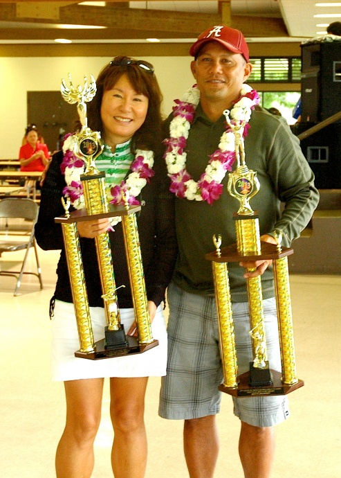 Maui Aloha Golf Classic overall gross champions Mia Hew (left) and Vernon Patao hold up their championship hardware for winning the women's and men's divisions, respectfully. Photo courtesy of Gail Tanaka.