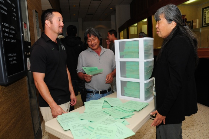 Kurt Yamamura, an HC&S employee; Warren Watanabe, from the Maui County Farm Bureau; and Mae Nakahata, an HC&S agronomist were among those in attendance at the committee hearing on Tuesday. The green cards shown are petitions signed by residents in opposition to the bill.