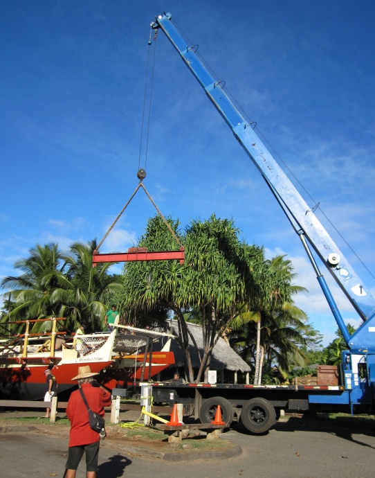 """Diversified Crane Inc. lifts and weighs Moʻokiha o Piʻilani Hawaiian voyaging canoe at 20,300 pounds. On the canoe are Captain Timi Gilliom and Puaita Pulotu; in the foreground, Dave Drown and Dr. George Harker, """"Dr. Leisure"""" filming the event.  Photo by Katherine Kamaʻemaʻe Smith."""