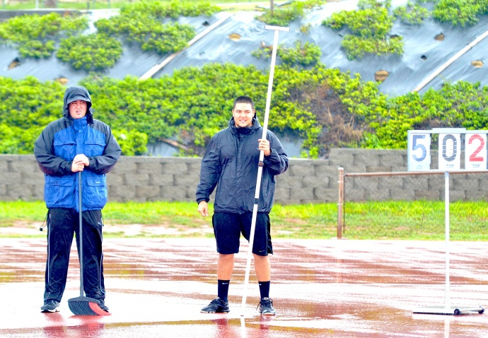 Kamehameha Schools Maui  head football coach Cody Nakamura (right) and offensive coordinator Jordan Helle try to stay dry while helping to officiate the high jump Saturday at the finals of the MIL Yamamoto Invitational Track & Field Meet. Photo by Rodney S. Yap.
