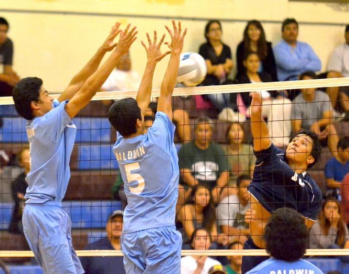 Kamehameha Maui's Tana Tua hits into the block of Baldwin's Ryan Garces (left) and Atreil Tanaka (5) Wednesday at the Jon Garcia Gym. Photo by Rodney S. Yap.
