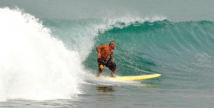 An unidentified male surfer goes backside on a wave Saturday afternoon in Kahului Harbor. Photo by Rodney S. Yap.