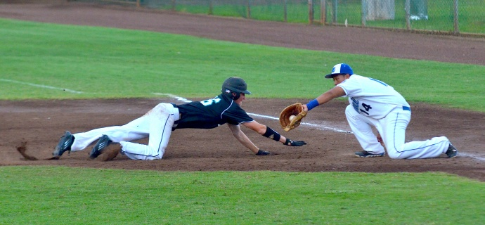 Maui High School's Chazz Ishikawa prepares to tag out King Kekaulike's Ryley Widell on a pick off at first base. Photo by Rodney S. Yap.