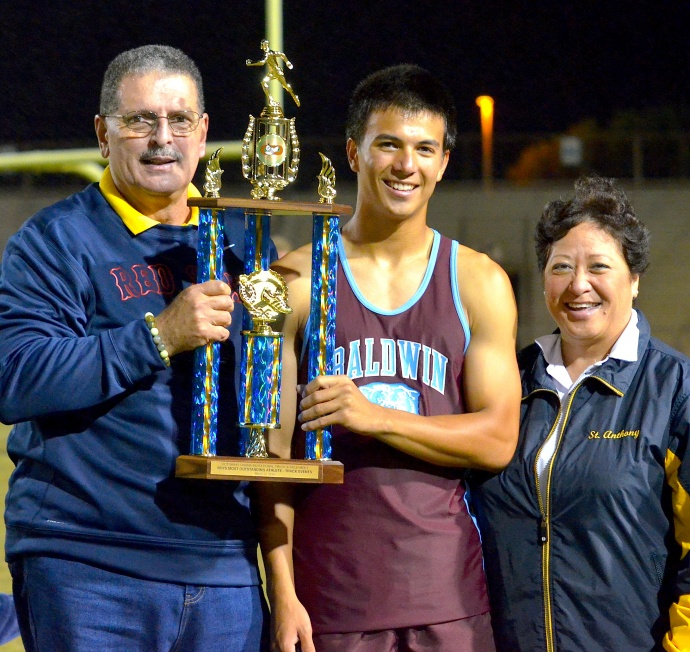 Baldwin's Dylan Leigh shows off his winning hardware for being named the most outstanding male runner at the 2014 Victorino Invitational Championships Saturday. Councilman Mike Victorino and wife, Jocelyn, pose with Leigh. The meet is annually hosted by St. Anthony Jr.-Sr. High School and sponsored by former Trojan sprinter and state champion Shane Victorino, now an outfielder for the Boston Red Sox. Photo by Rodney S. Yap.