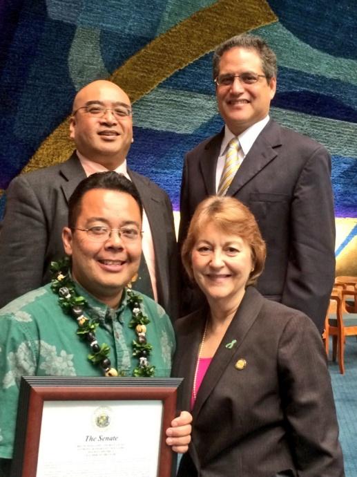 Photo Courtesy of Sen. J. Kalani English: Senators Gilbert Keith-Agaran (top left),  J. Kalani English (top right) and Roz Baker (bottom right) present Anthony Kamakaʻeu Williams (bottom left), 2014 Maui School District Teacher of the Year, with a congratulatory certificate from the Hawaiʻi State Senate.