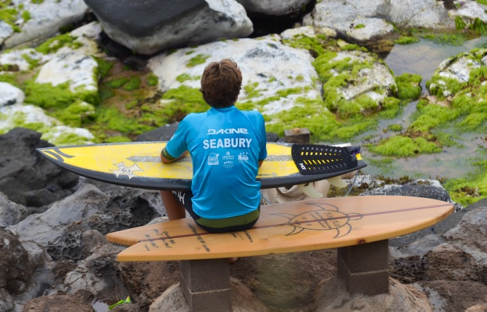 A Seabury Hall boys competitor watches the action in the water while awaiting the next heat of the boys shortboard competition Saturday. Rodney S. Yap.