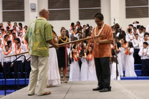 Vice Principal, Leo Delatori ties the winning class color on the ihe as Lance Cagasan (holding the ihe) and Jay-R Kaawa, High School Principals look on.  Photo courtesy, Lokelani Patrick/KSM