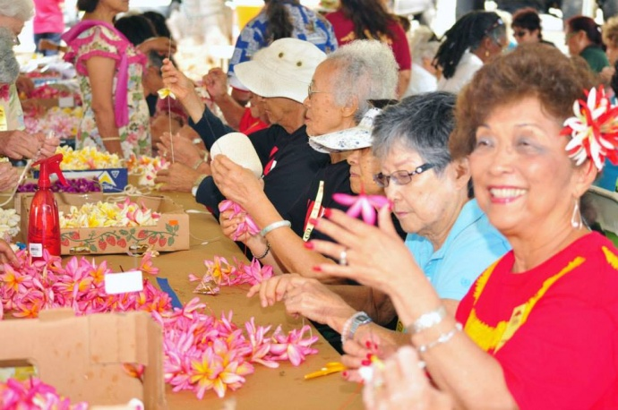 "Community participants sew lei to honor veterans at the 2013 ""Blossoms for the Brave"" event. File photo courtesy County of Maui."