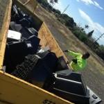 Road Crew member Kaulana Saltiban loads the Ecycling container. Photo courtesy Mālama Maui Nui.