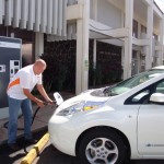 "Maui Electric's Troy Connatser demonstrates plugging in an electric vehicle to the island's first ""open access"" DC fast charger that is now open to the public at the company's Kahului office. Courtesy photo."