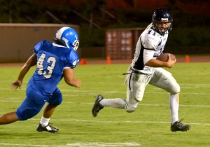 Kamehameha Maui quarterback Chase Newton (11) scrambles from the pursuit of Maui High's Josh Shirota (43). Photo by Rodney S. Yap.
