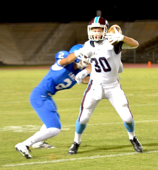 Baldwin's Dane Elf catches this pass from quarterback Tage Akaka-Foster during first-quarter action Friday against Maui High. The Sabers' Alani Malafu (2) defends on the play. Photo by Rodney S. Yap.