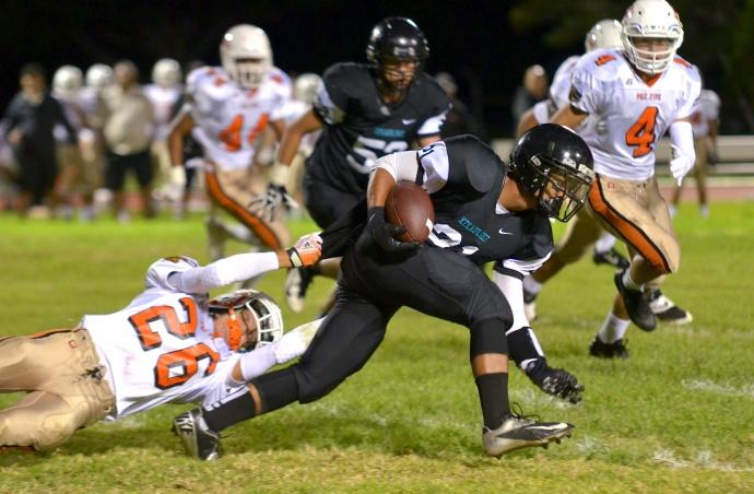 King Kekaulike's Jacob Ramos tries to break free from the grasp of Pac-Five defender Travis Miyashiro. Photo by Rodney S. Yap.