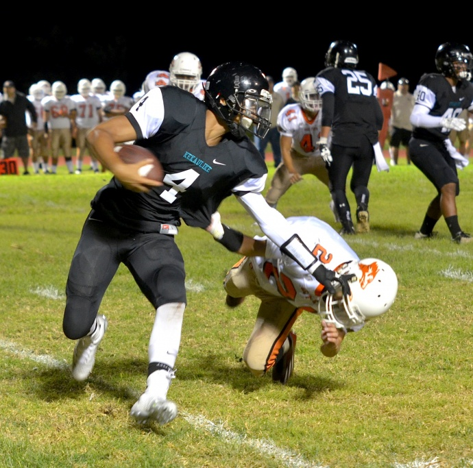 King Kekaulike quarterback Kawika Homalon (4) tries to stiff-arm a defender during first-half action Saturday against Pac-Five. Photo by Rodney S. Yap.