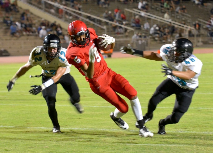 Lahainaluna wide receiver Isaiah Biga-Rogers splits a pair of King Kekaulike defenders — Josh Ogata (12) and Izaiah Manrique (48) — en route to a 13-yard touchdown reception Friday at War Memorial Stadium. Photo by Rodney S. Yap.