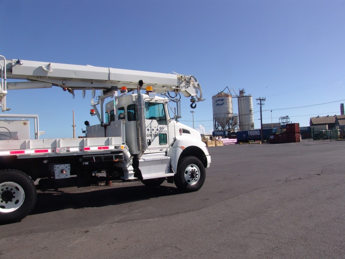 Maui Electric boom trucks heading to assist in power restorations on Hawai'i Island were loaded onto the Young Brothers Maka'ala barge in Kahului this morning (Aug. 12). Maui Electric crews will arrive tomorrow to help in the restoration efforts. Courtesy photo.
