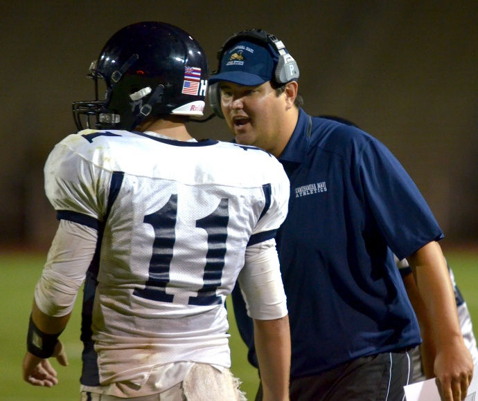 Kamehameha Maui coach Jordan Helle instructs Chase Newton on the sidelines during an MIL game last season. Photo by Rodney S. Yap.