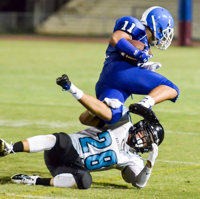 Maui High's Jayden Wilhelm (11) is upended by a King Kekaulike defender during first-half action Saturday. Photo by Rodney S. Yap.