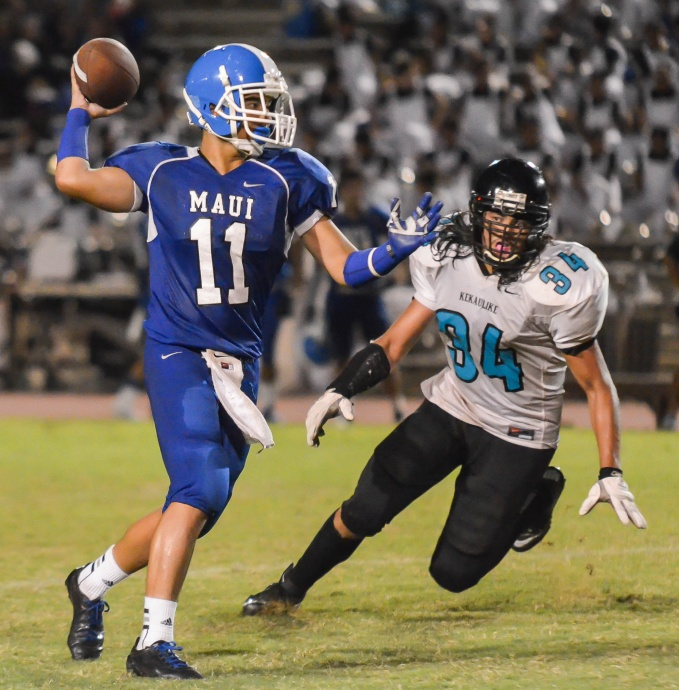 Maui High's Jayden Wilhelm (11) prepares to throw a pass while getting backside pressure from King Kekaulike's Kanoa Awai-Dickson.