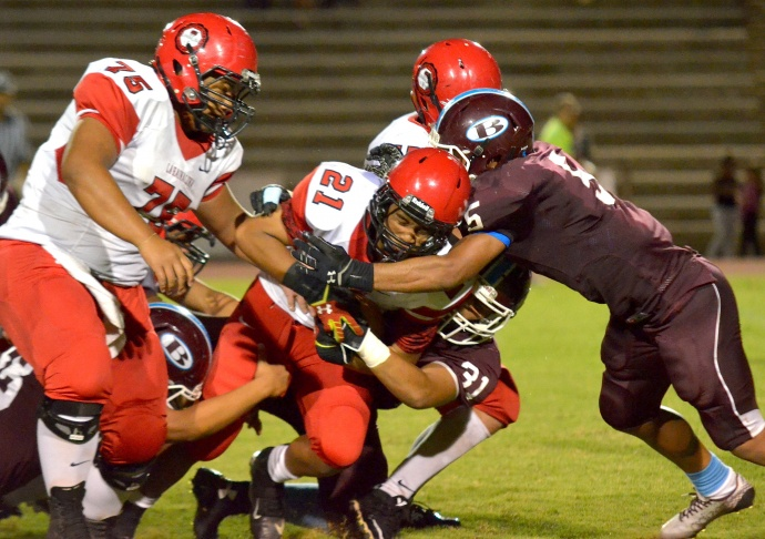 Lahainaluna sophomore running back Donavon Defang (21) moves the pile and Baldwin defenders Kailoa Ambrose (31) and Kawena Alo-Kaonohi. Photo by Rodney S. Yap.