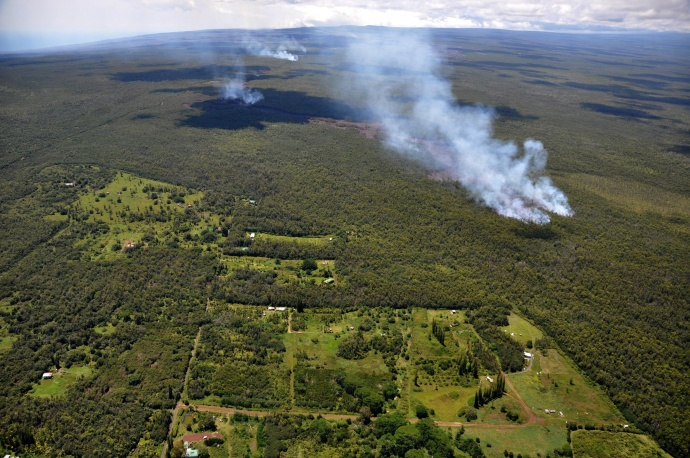 As of Friday afternoon, September 12, 2014, the most distal front of the June 27th lava flow had reached a straight-line distance of 14.9 km (9.3 miles) from the source vent on the northeast flank of the Puʻu ʻŌʻō cone. The flow has continued in the northeast direction that it assumed in the middle of the week and is now only 171 meters (0.1 miles) from the boundary of the Kaohe Homesteads community. The flow is still within thick forest, so that dense plumes of smoke are created as vegetation is consumed. Small breakouts (visible as plumes in the middle distance) are also active closer to Puʻu ʻŌʻō, roughly midway along the length of the June 27th flow. Photo courtesy Hawaiian Volcano Observatory, USGS.