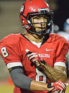 Lahainaluna quarterback Makoa Sione Filikitonga-Lukea takes off his defensive gloves before switching  to offense against Baldwin last Saturday. Photo by Rodney S. Yap.