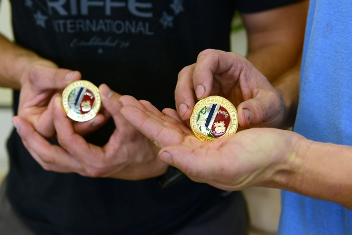 3rd Mate Justin Moore and 2nd Engineer Josef Eggert of the motor vessel Manukai, show challenge coins given to them from Rear Adm. Cari Thomas, 14th Coast Guard District commander, after being presented a Meritorious Public Service award at the Matson terminal on Sand Island in Honolulu, Nov. 24, 2014. The crew was presented the award for the rescue of the three men from the 42-foot sailboat Walkabout caught in Hurricane Julio 414 miles northeast of Oahu, Aug. 10, 2014. (U.S. Coast Guard photo by Petty Officer 2nd Class Tara Molle)