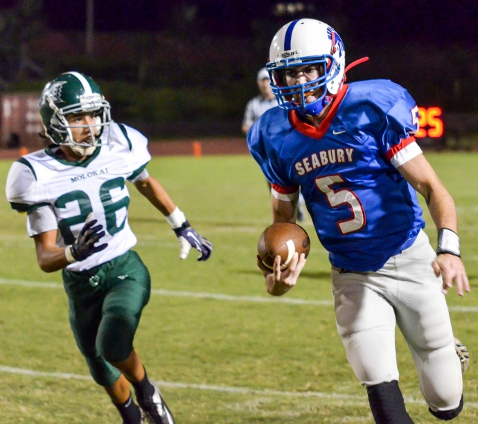 Seabury Hall's Jaxson Stinger gets into the open field en route to a long touchdown run. Molokai's Cody Pestana-Stone gives chase. Photo by Rodney S. Yap.
