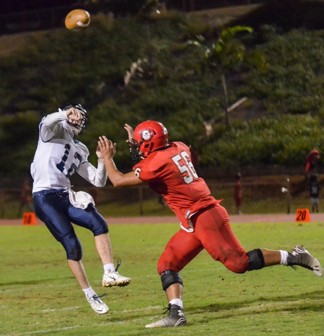 Kamehameha Hawaii quarterback Micah Kanehailua delivers this pass under pressure from Lahainaluna's Peni Taufa. Photo by Rodney S. Yap.