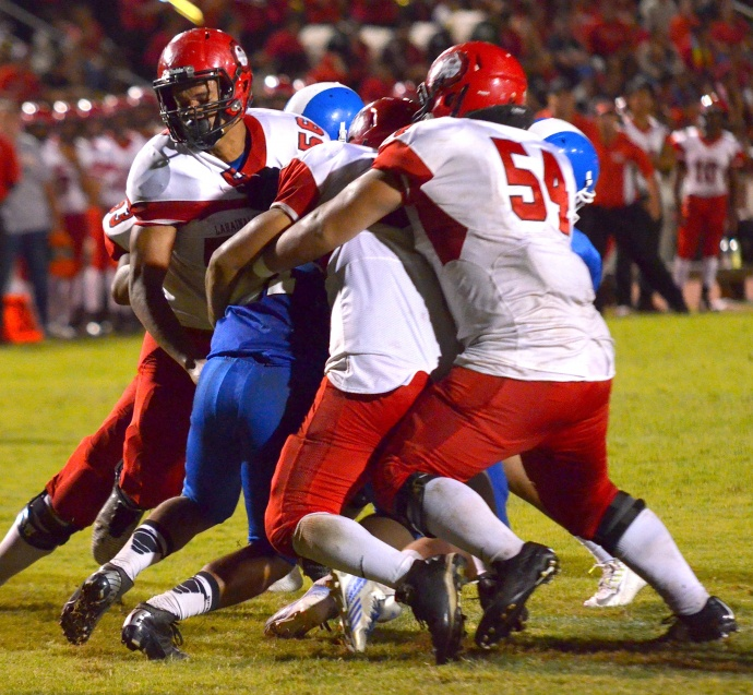 Lahainaluna's defense, led by Peni Taufa (56), Connor Mowat (54) and Ken Brito will showcase its skills today against Kamehameha Hawaii. Here they are seen wrapping up a Maui High running back during a recent game at War Memorial Stadium. File photo by Rodney S. Yap.