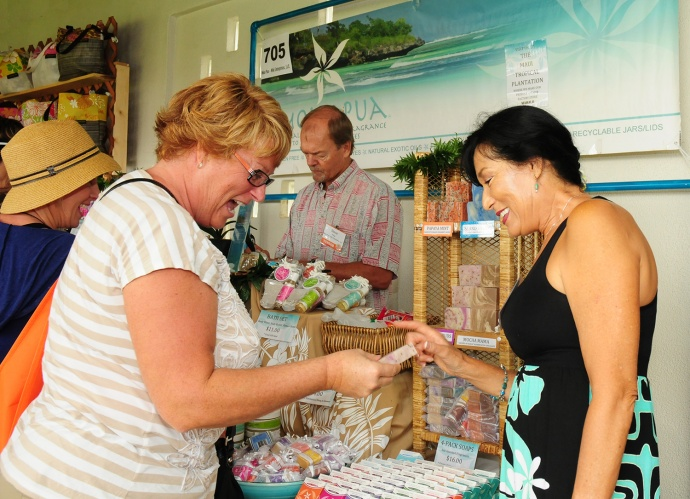 """Lori Hintzsche of Phoenix, Ariz., looks over a product made by Vicki Pillar of Moku Pua during the Made in Maui County Festival held Saturday at the Maui Arts & Cultural Center. Pillar said  business was """"exploding,"""" and that she and her husband, Steve, picked up five new wholesale accounts and a steady stream of local customers and Maui visitors."""