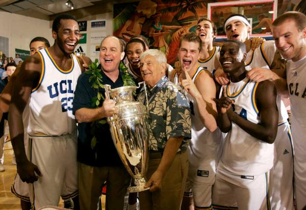 In this Nov. 22, 2006 photo, UCLA coach Ben Howland, second from left, and his team is presented with the championship trophy by Wayne Duke, tournament chairmen emeritus, after UCLA defeated Georgia Tech 88-73 in the championship game at the Maui Invitational college basketball tournament in Lahaina. AP File Photo/Michael Conroy.